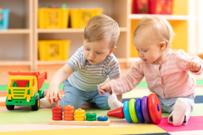 Preschool boy and girl playing on floor with educational toys